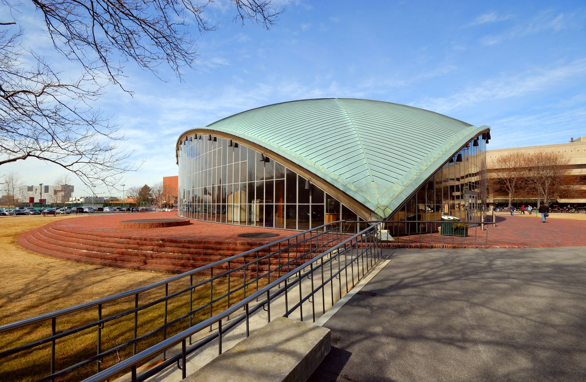 The exterior of the Kresge Auditorium in Massachusetts. The roof is green and sloped. The walls are glass.