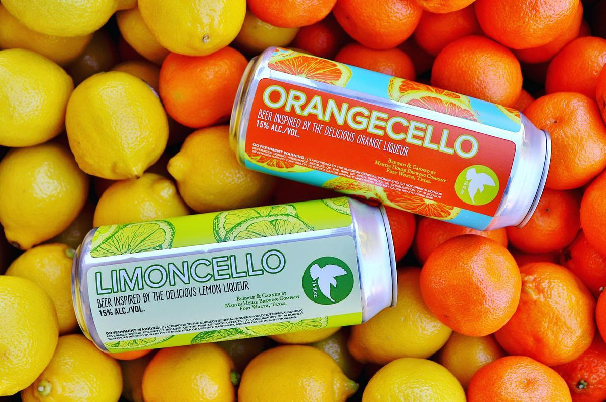 Cans of Limoncello and Orangecello beer on a bed of oranges and lemons