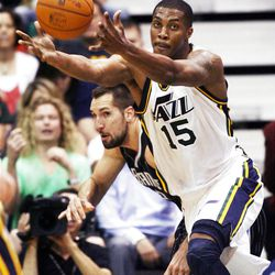 Utah Jazz forward Derrick Favors (15) grabs a rebound with Orlando's #33 Ryan Anderson coming up from behind as the Utah Jazz and the Orlando Magic play Saturday, April 21, 2012 in Energy Solutions arena.
