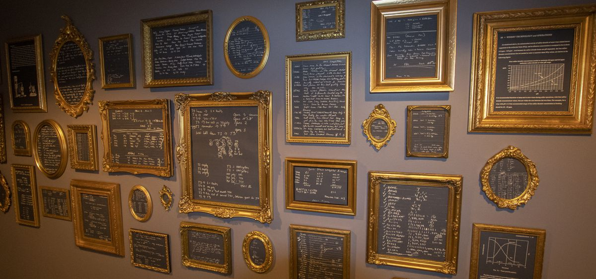 A wall of chalkboard wine analyses and charts, all displayed in gold frames.