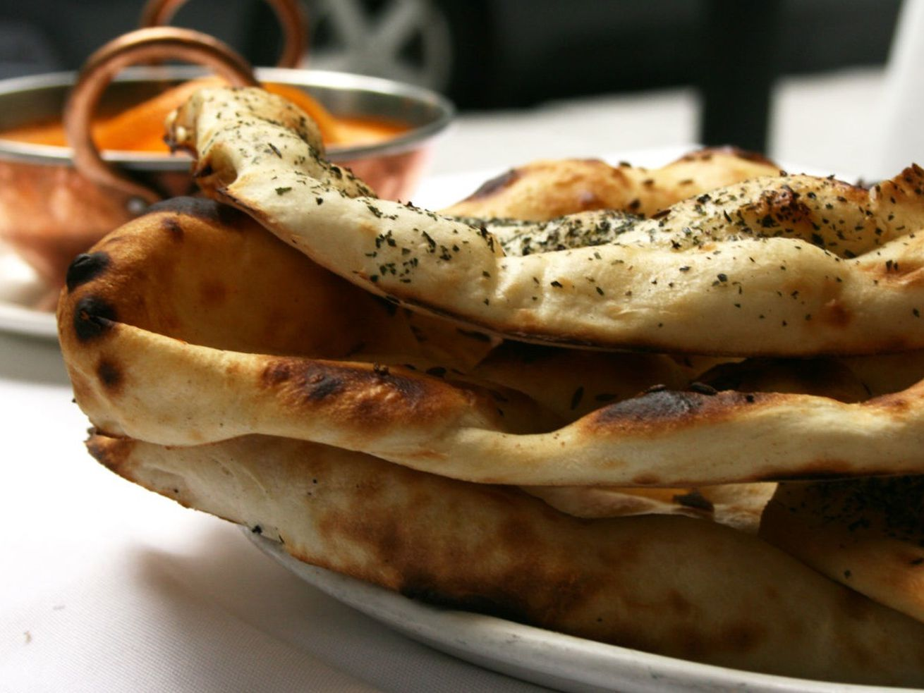 naan with bowl of curry in the background