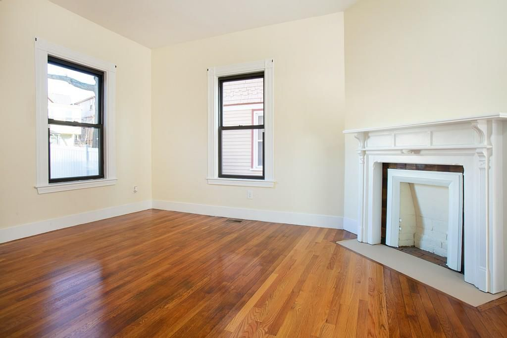 An empty room with a fireplace and two windows.