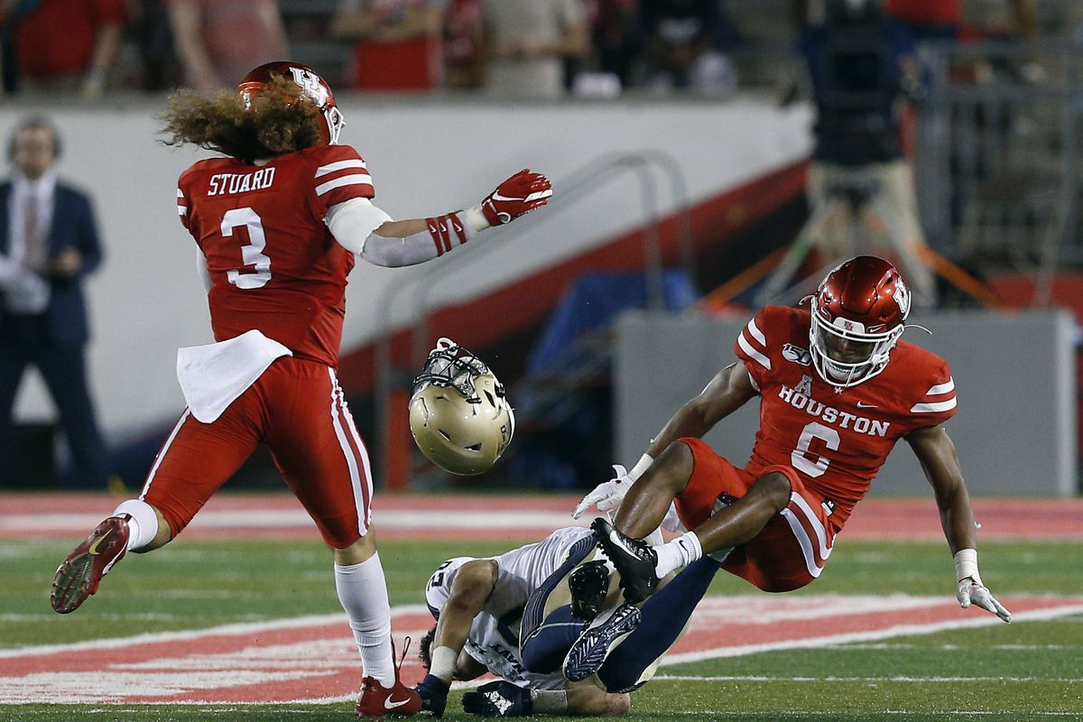 Keoni-Kordell Makekau of the Navy Midshipmen loses his helmet and the ball as he takes a hit from Damarion Williams of the Houston Cougars during the third quarter on November 30, 2019 in Houston, Texas.