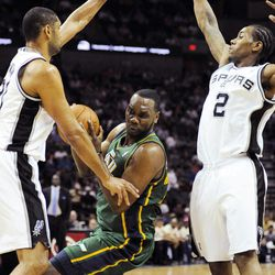 Utah Jazz's Al Jefferson, center, is defended by San Antonio Spurs' Tim Duncan, left, and Kawhi Leonard during the first half of an NBA basketball game, Sunday, April 8, 2012, in San Antonio.