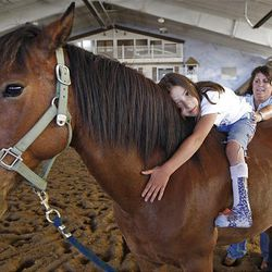 Gennaveve Dilley, 9, hugs Ziggy as Cindy Becker helps her at the Buffalo Ranch in Farmington on Thursday as part of a therapeutic riding program organized by the nonprofit group Therapeutic Assets.