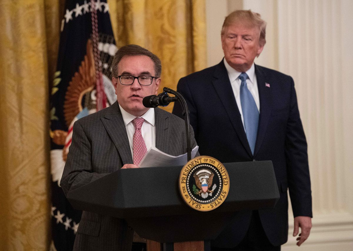EPA Administrator Andrew Wheeler speaking from a podium, with President Trump behind him.