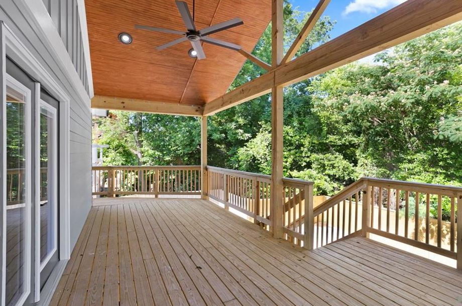 A huge deck with a ceiling fan overhead.