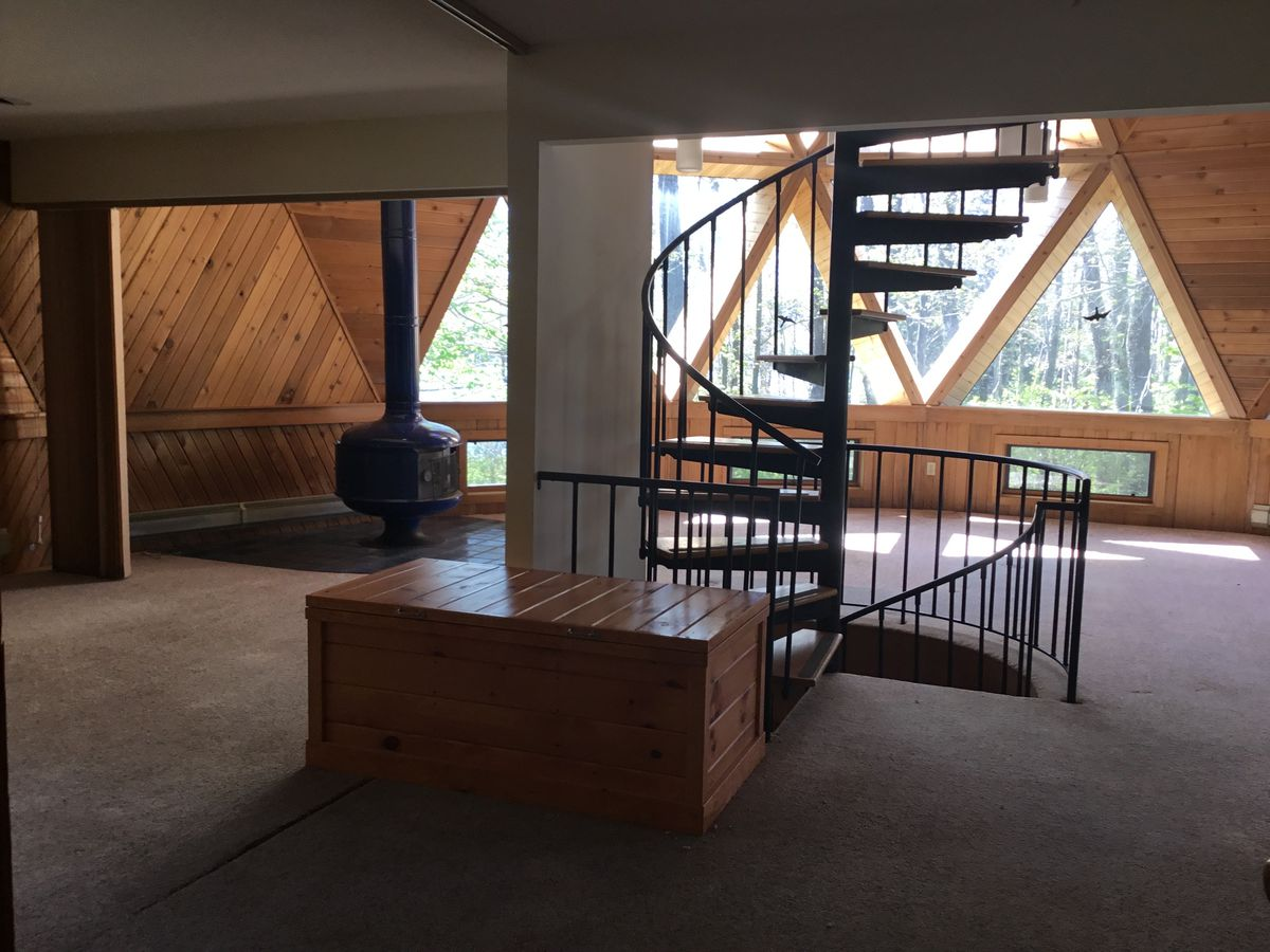 An interior view of a geodesic dome home pre-renovation, featuring carpeted floors and timber-paneled walls.