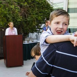 Dash Johnson, 4, a patient at Primary Children's Hospital, is held by his father during the reopening of the Angel Garden at the hospital in Salt Lake City on Monday, Aug. 1, 2016. The redesigned garden includes more than 1,000 new plants and trees, as well as legacy monuments, including the Butterfly Angel statue, a commissioned 5-foot bronze. Dash's family spearheaded renewal project.