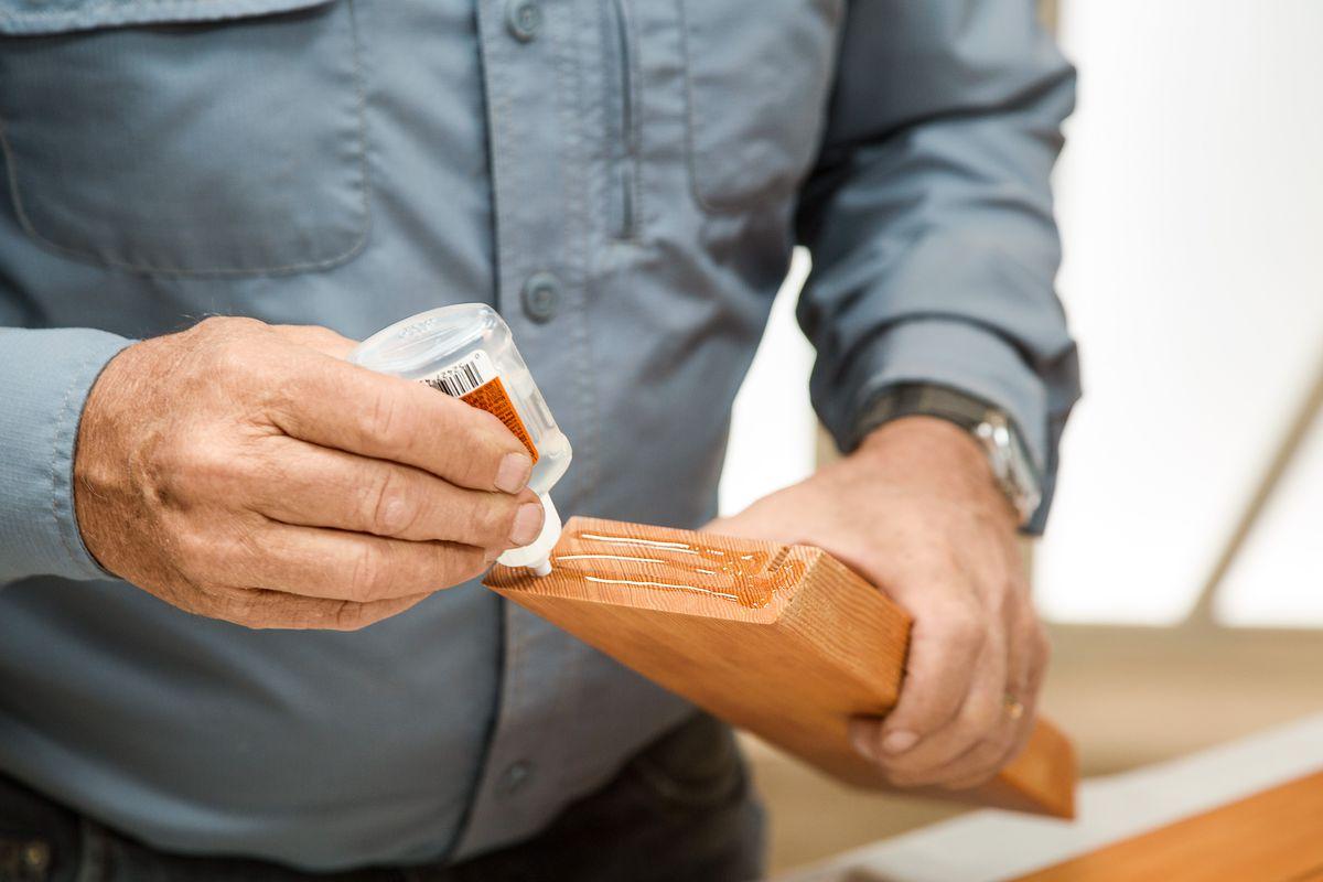 Pessoa segurando um painel de madeira e aplicando cola em 3 linhas até o final.