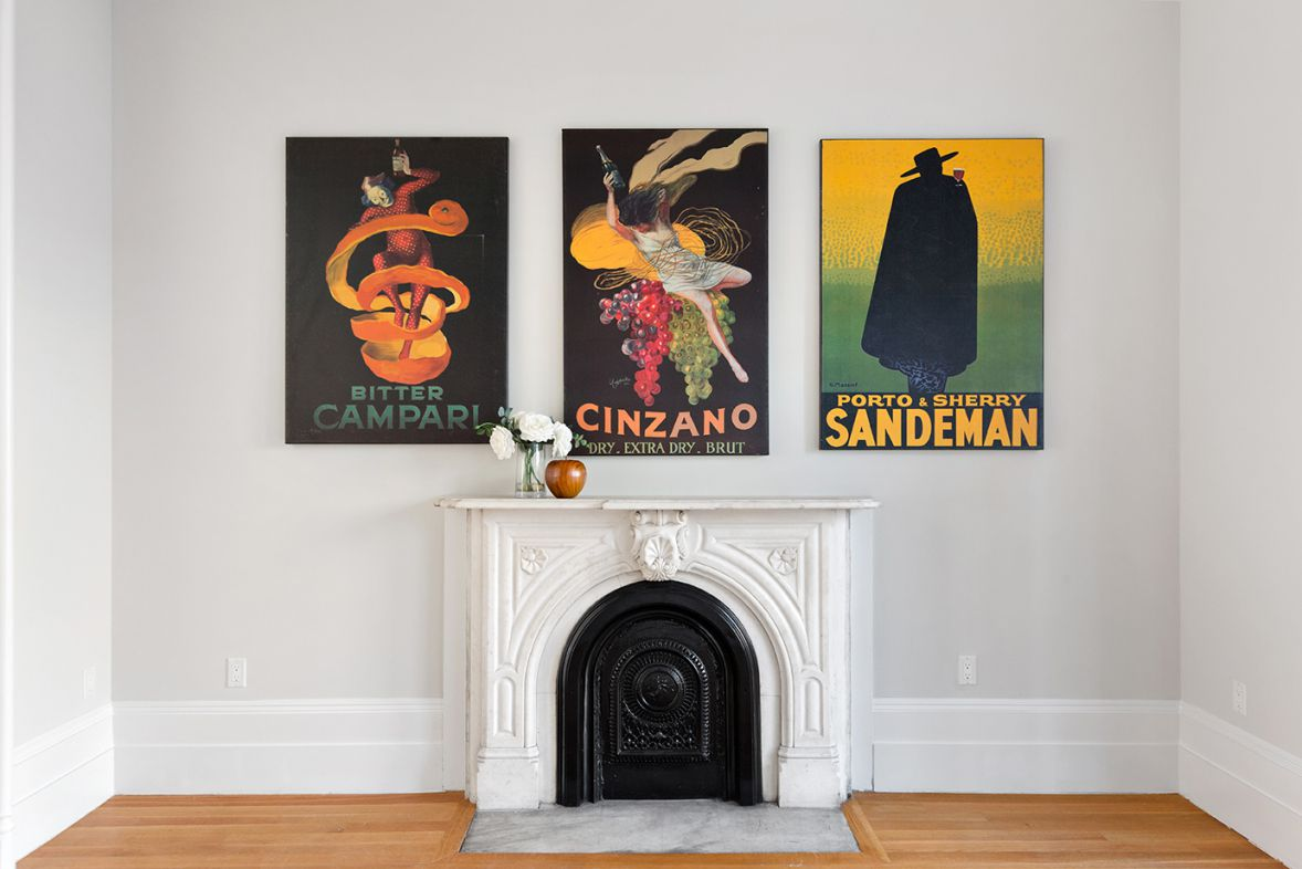 A living area with light grey walls, hardwood floors, a fireplace with a mantle, and three colorful posters hanging on the wall.