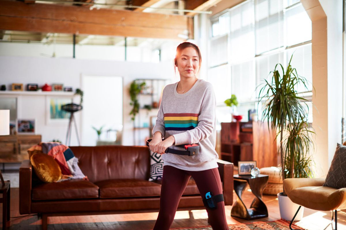 a young Asian woman wearing a gray sweatshirt and burgundy exercise pants playing Ring Fit Adventure in a brightly lit loft apartment, holding the Ring-Con peripheral in her hands