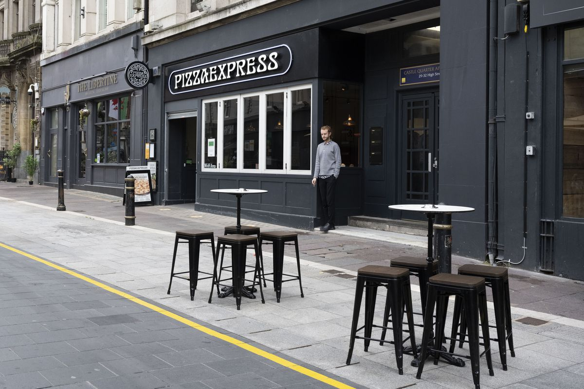Empty tables on a pavement outside a Pizza Express restaurant