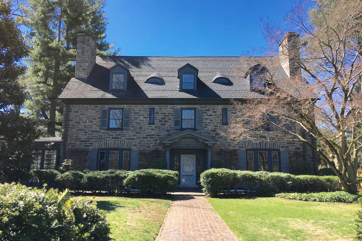 A stone Colonial Revival home with periwinkle blue shutters.