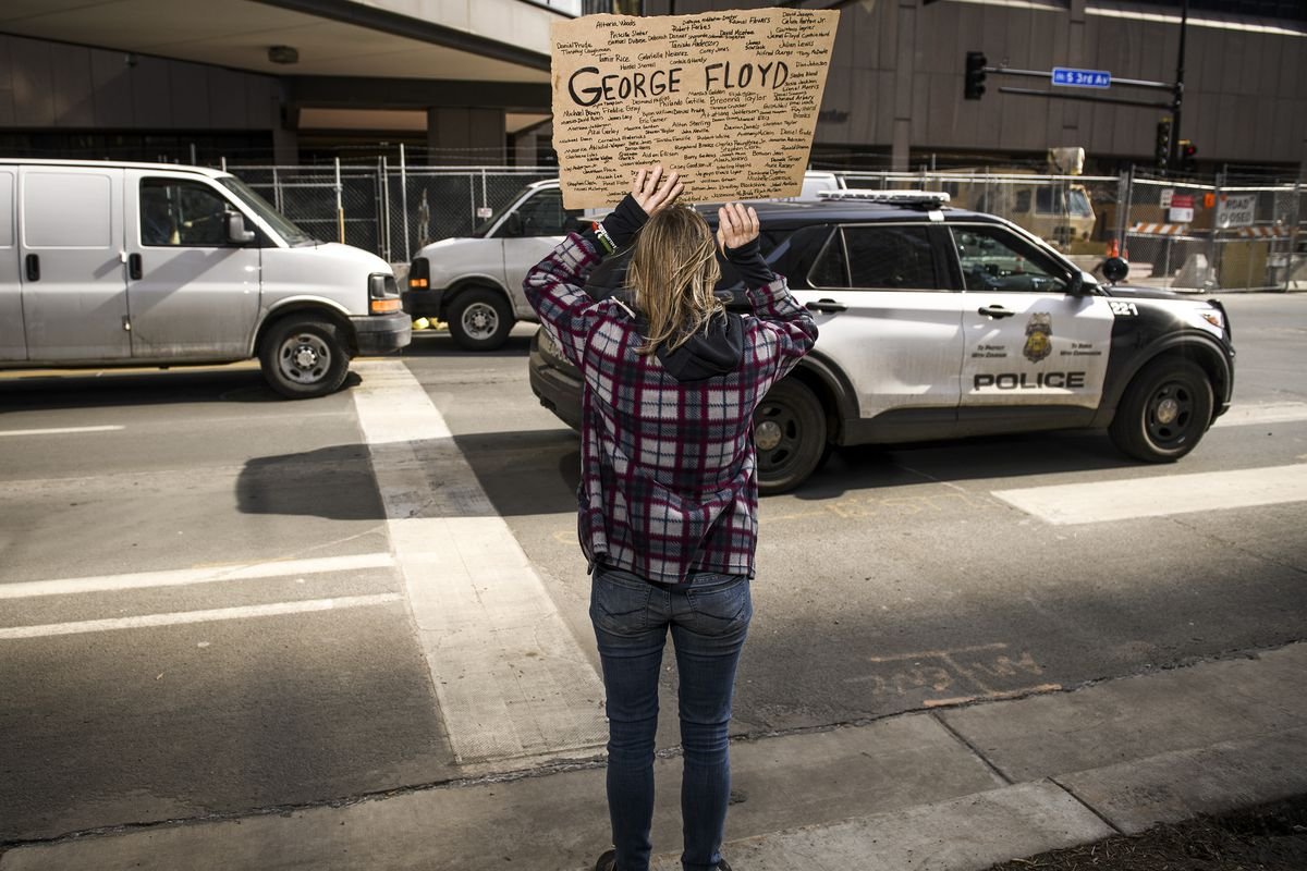 """A person with long brown hair and their back to the camera holds a sign above their head. Near the top, in bold black letters is the name """"George Floyd."""" Floyd's name is surround by dozens of other handwritten names of those who have faced police violence."""