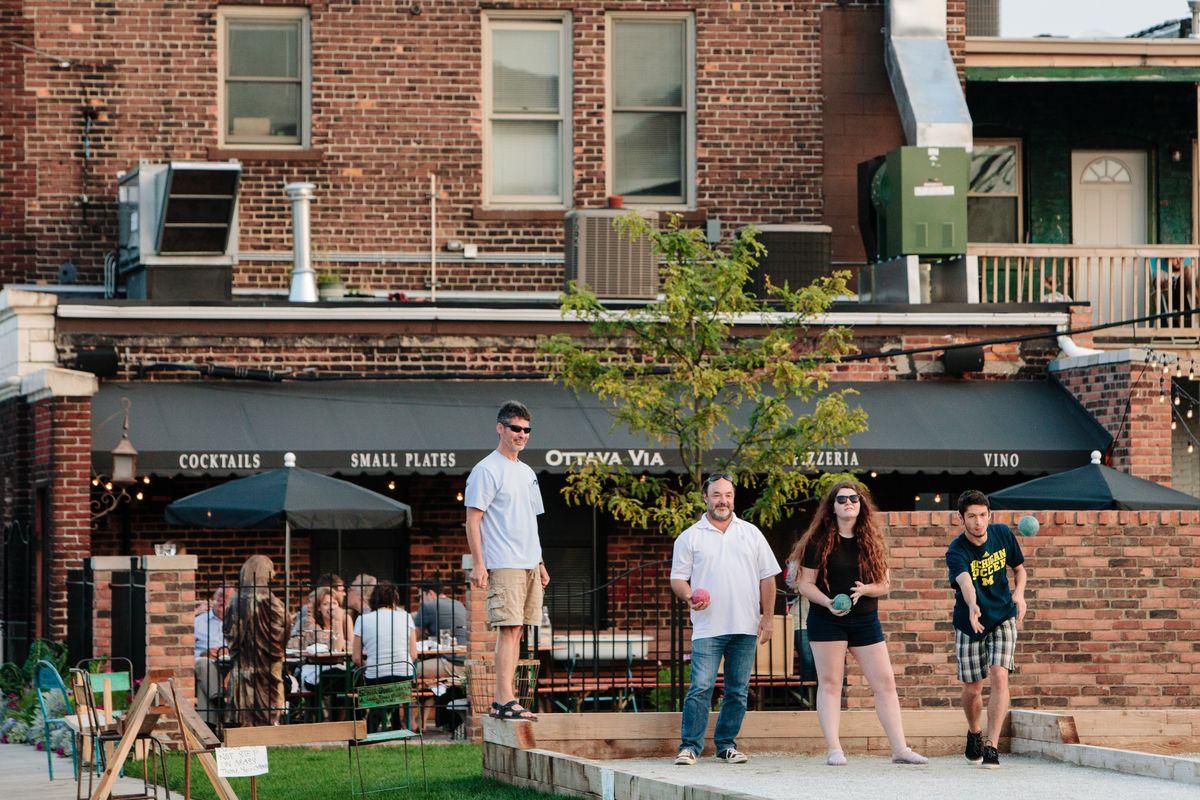 A family plays bocce ball on the patio behind Ottava Via's brick building.