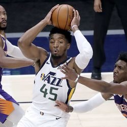 Utah Jazz guard Donovan Mitchell (45) looks to make a pass between Phoenix Suns guard Jevon Carter (4) and Phoenix Suns guard Langston Galloway (2) during a preseason NBA game at the Vivint Smart Home Arena in Salt Lake City on Monday, Dec. 14, 2020. The Jazz beat the Suns 111-92.