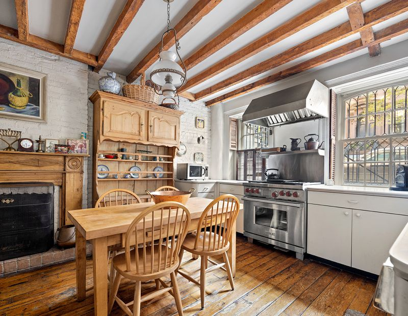A kitchen with wood panels in its ceilings and exposed brick.