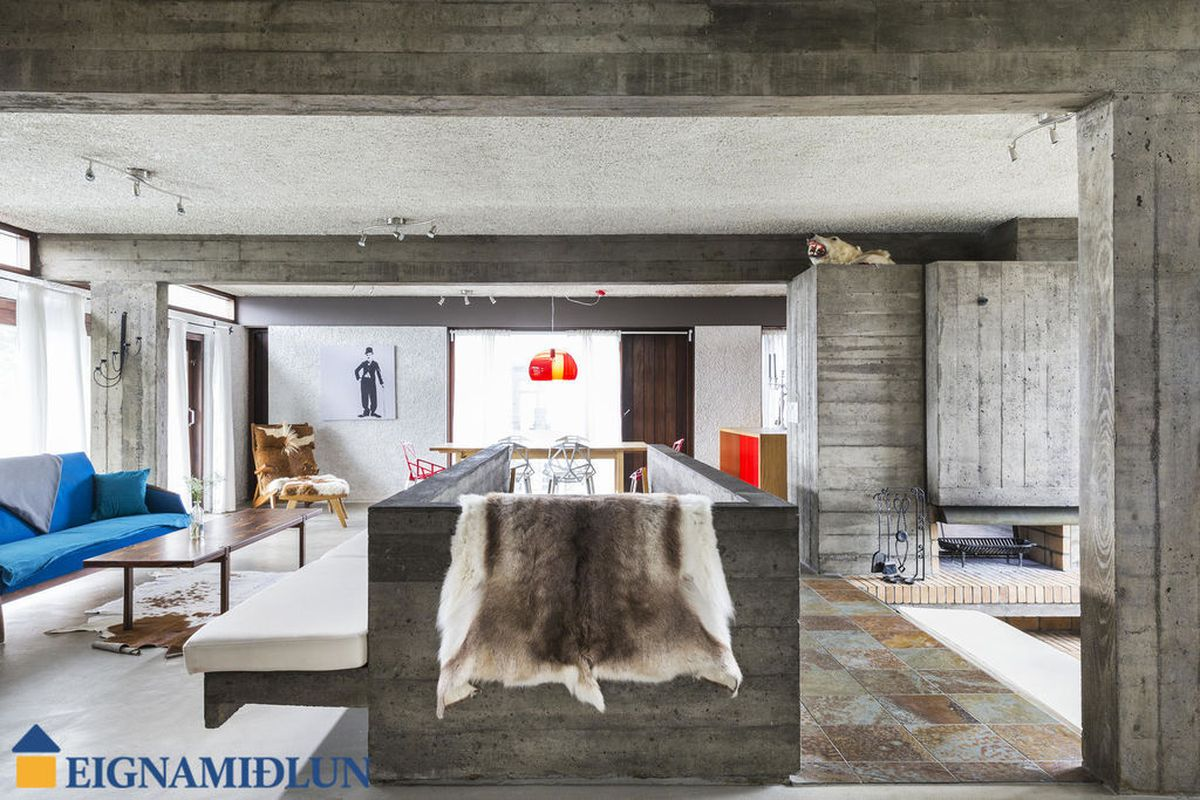 Interior shot of main floor looking toward dining area, with lounge on the left side and a conversation pit with massive concrete fireplace on the other and a concrete stairwell dividing the two spaces.