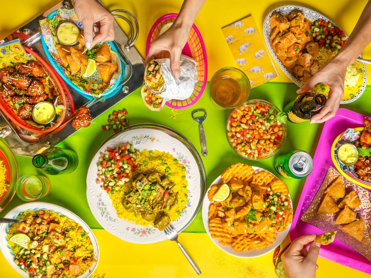 a variety of brightly colored dishes with food on them onto of a yellow background