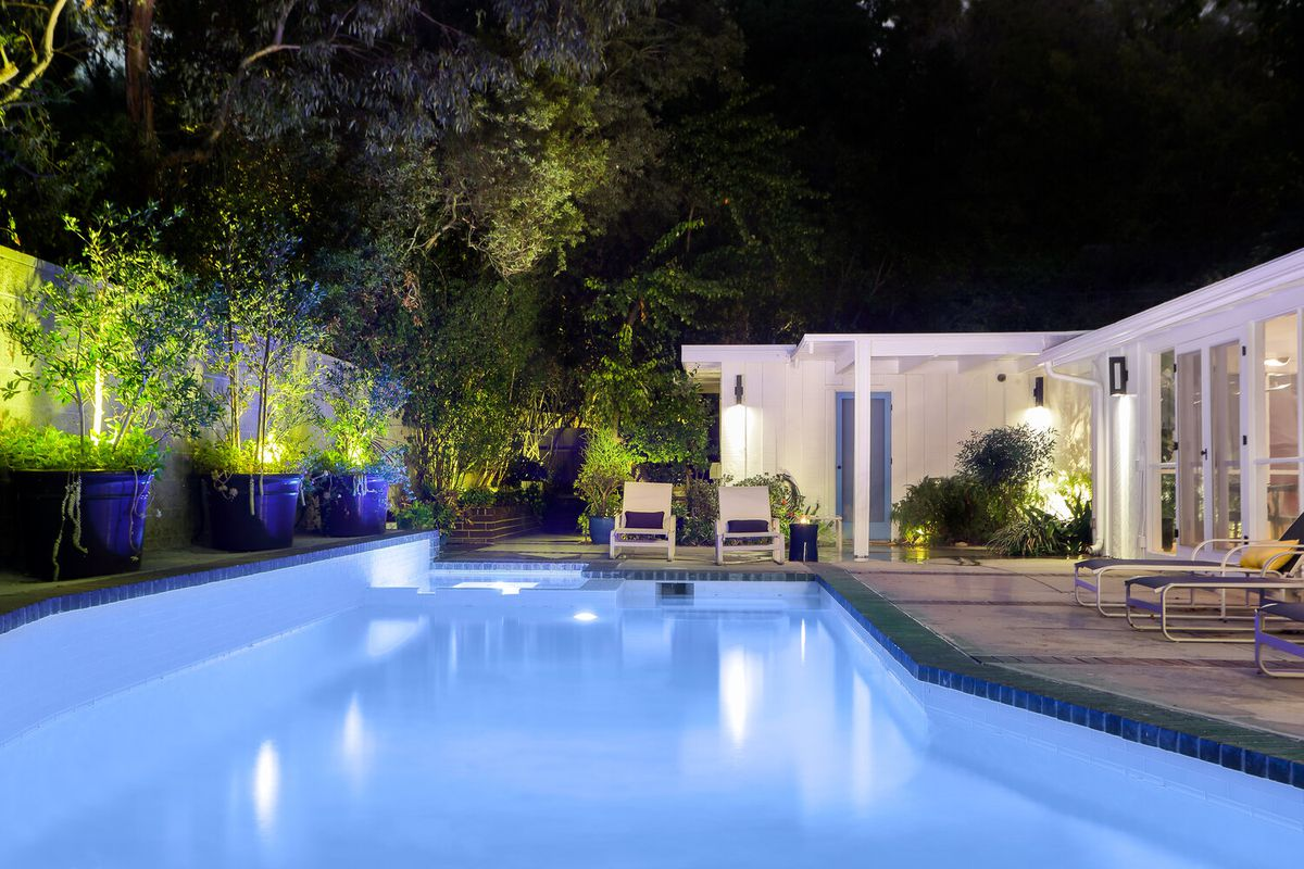 A nighttime photo of the pool, lit up, and accent lights on the potted trees on a ledge overlooking the pool. The yard is backed by tall trees that shield the pool.