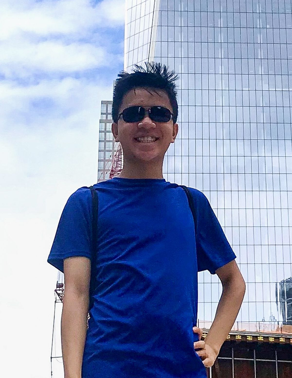 A young man wearing a blue shirt and sunglasses poses for a portrait, in front of skyscrapers in New York City.