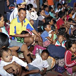 Residents take shelter at the lobby of the city hall in Tandag, Surigao Del Sur province in southern Philippines, following a 7.6 magnitude earthquake that struck eastern and southern Philippines, Friday, Aug. 31, 2012. The quake set off car alarms, shook items off shelves and sent many coastal residents fleeing for high ground before the Pacific Tsunami Warning Center lifted all tsunami alerts it had issued for the Philippines and neighboring countries from Indonesia to Japan, and for Pacific islands as far away as the Northern Marianas.