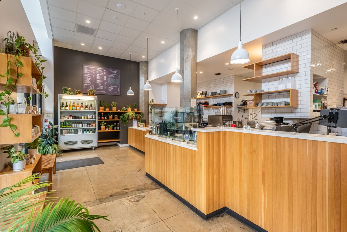 A tilted angle of a wooden and cement coffee shop with house plants.