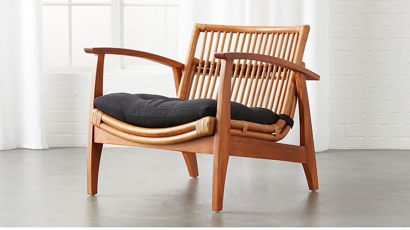 A rattan arm chair with an open-slated back, high arms, a curved seat, and black cushion.