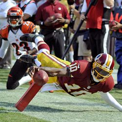 Washington Redskins quarterback Robert Griffin III is knocked out of boards shy of the goal line during the second half of an NFL football game against Cincinnati Bengals in Landover, Md., Sunday, Sept. 23, 2012.