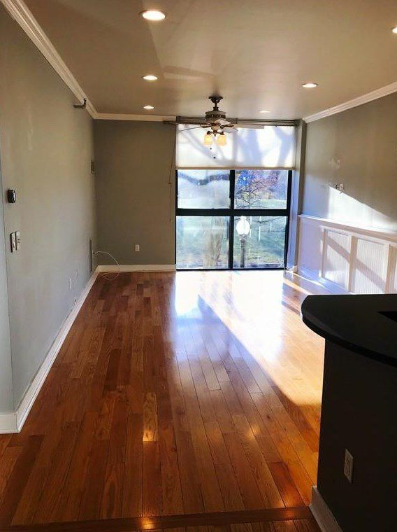 An empty, narrow living room with large windows at the end.
