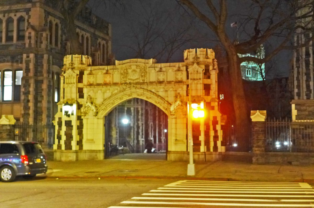 An ornate white gate leads to the gray buildings of City College, seen at night.