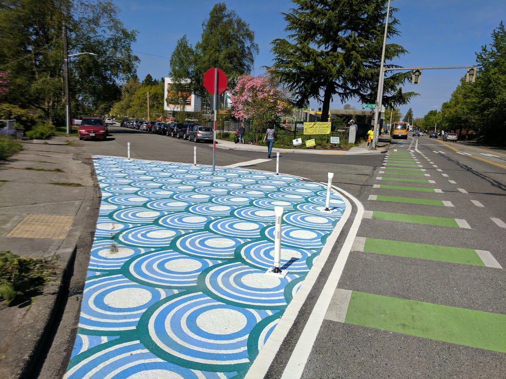 A brightly blue painted pattern covers a part of the street cordoned off by posts at an intersection.