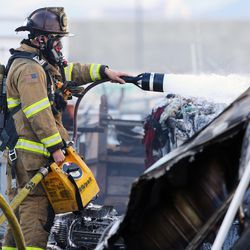 A West Valley City firefighter spreads foam on hot spots at a junkyard fire at 5600 West 2300 South on Monday, Oct. 17, 2016.