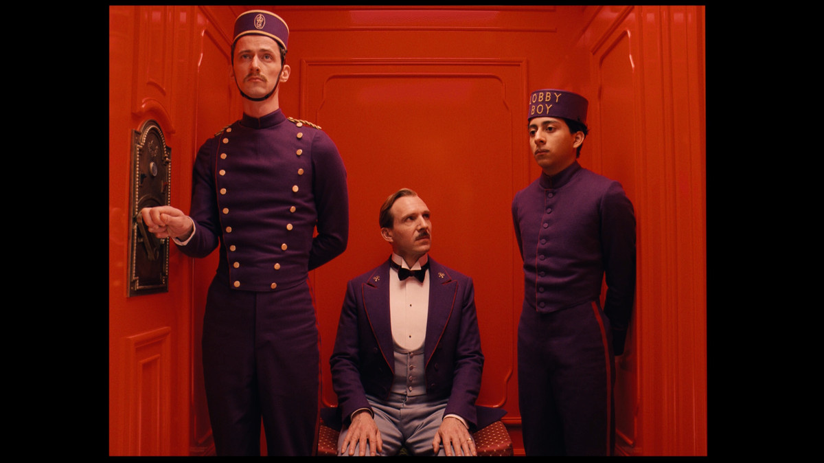 two bellhops and a seated maître d'  ride up a bright red elevator