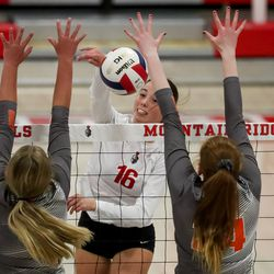 Mountain Ridge's Kelli Wright spikes the ball between Skyridge's Olivia Marshall and Abbigail Alvord in a girls volleyball match in Herriman on Tuesday, Sept. 7, 2021.