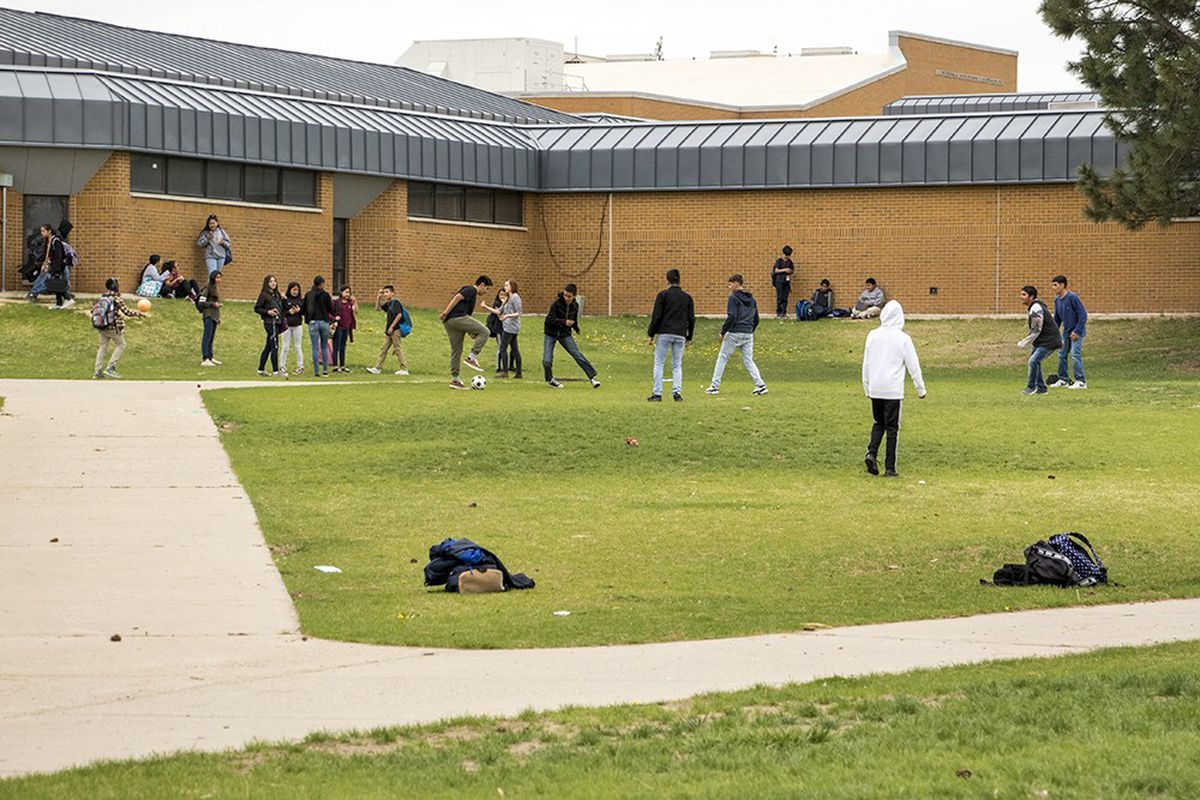 Students stand on the lawn of a high school.