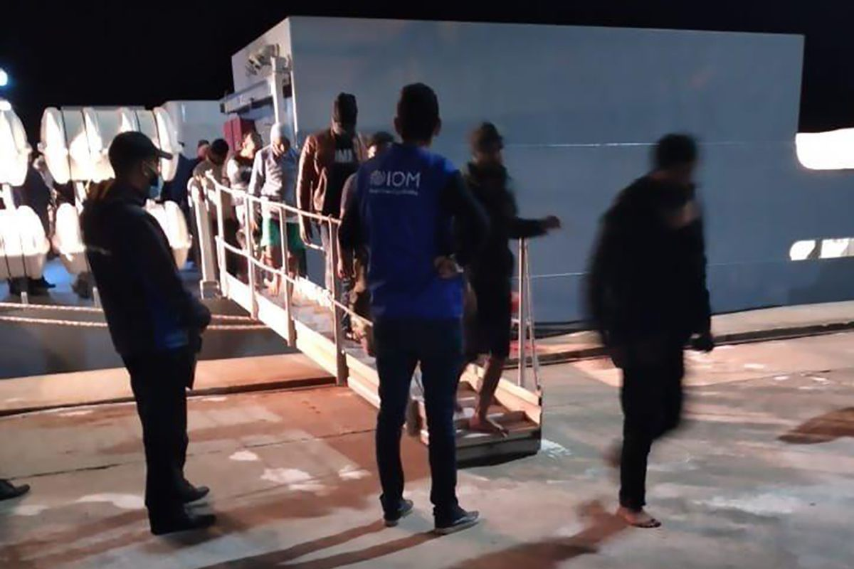 This photo provided by the International Organisation for Migration (IOM) Tunisia shows migrants disembarking in Tunisia, late Monday, May 17, 2021. Tunisian authorities say more than 50 migrants have drowned off the coast of the North African country, while 33 others were rescued by workers from an oil platform.