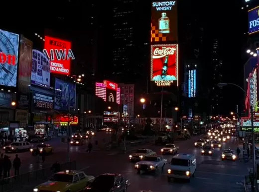 Times Square at night. There are multiple lit billboards and many cars.