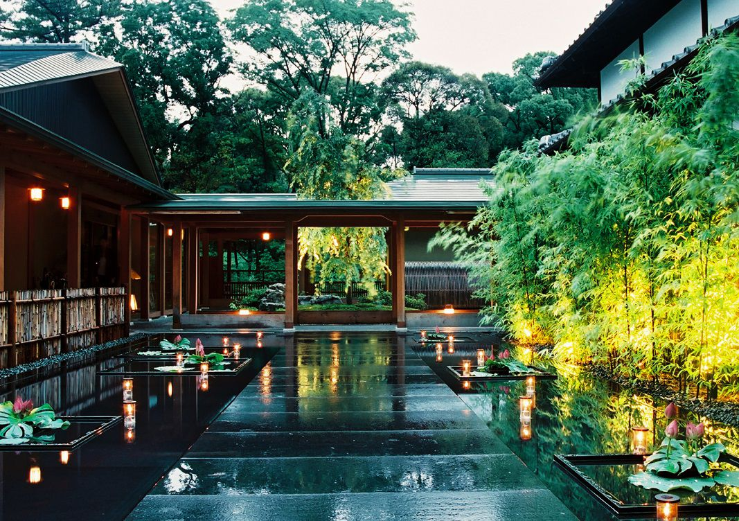 The courtyard of a Tokugawa residence, with shallow pools topped with plants and lanterns, tall plants to one side and large trees in the background ahead, a covered walkway between two structures
