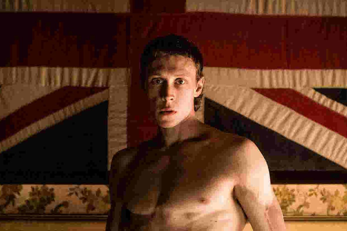 A young man stands shirtless in front of a UK flag.