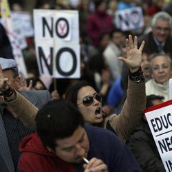 A woman shouts slogans against Spanish government during a demonstration against health and education cuts recently announced by the Spanish government, in Madrid, Spain, Sunday, April 15, 2012.