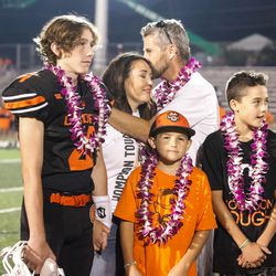 """Ogden football coach Erik Thompson, who was recently diagnosed with Lou Gehrig's disease, kisses his wife as he celebrates with his supporters after a high school football game billed as """"Erik Thompson Night"""" on Friday, Sept. 3, 2021, at Ogden High School in Ogden."""