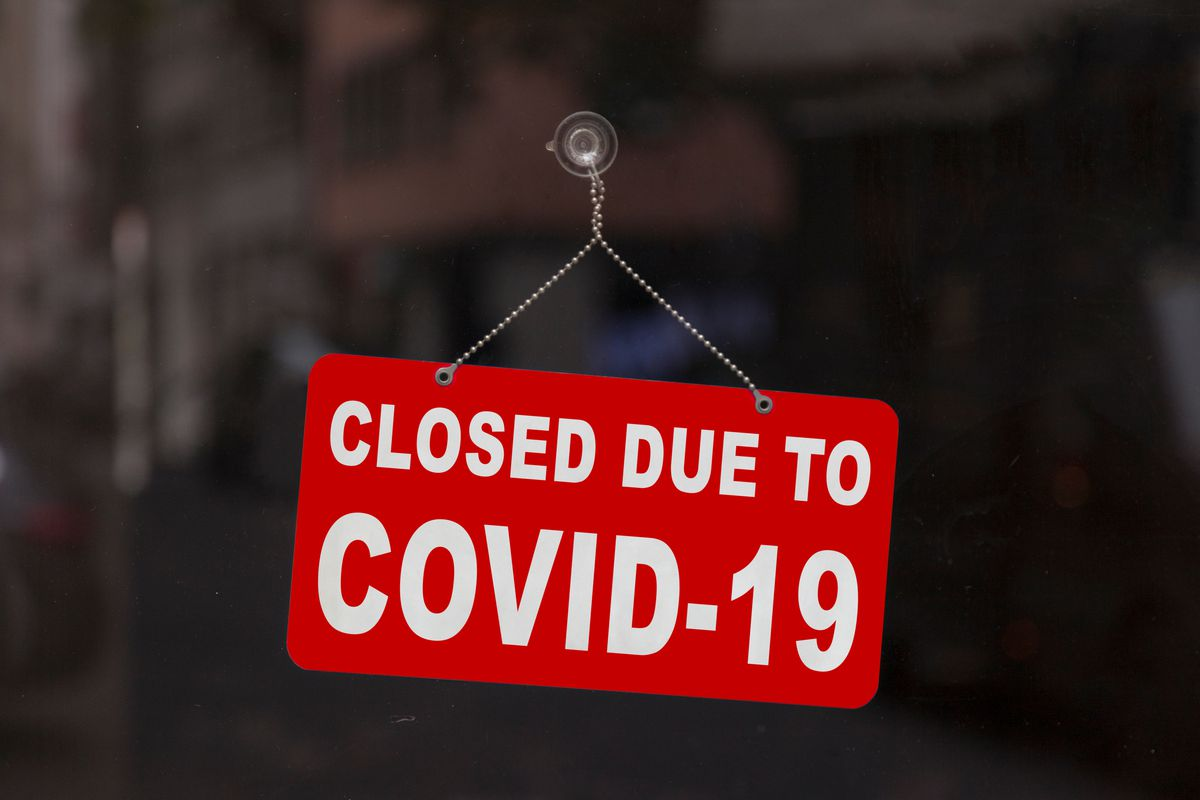 """A red sign on a restaurant window says, """"Closed Due to COVID-19."""""""