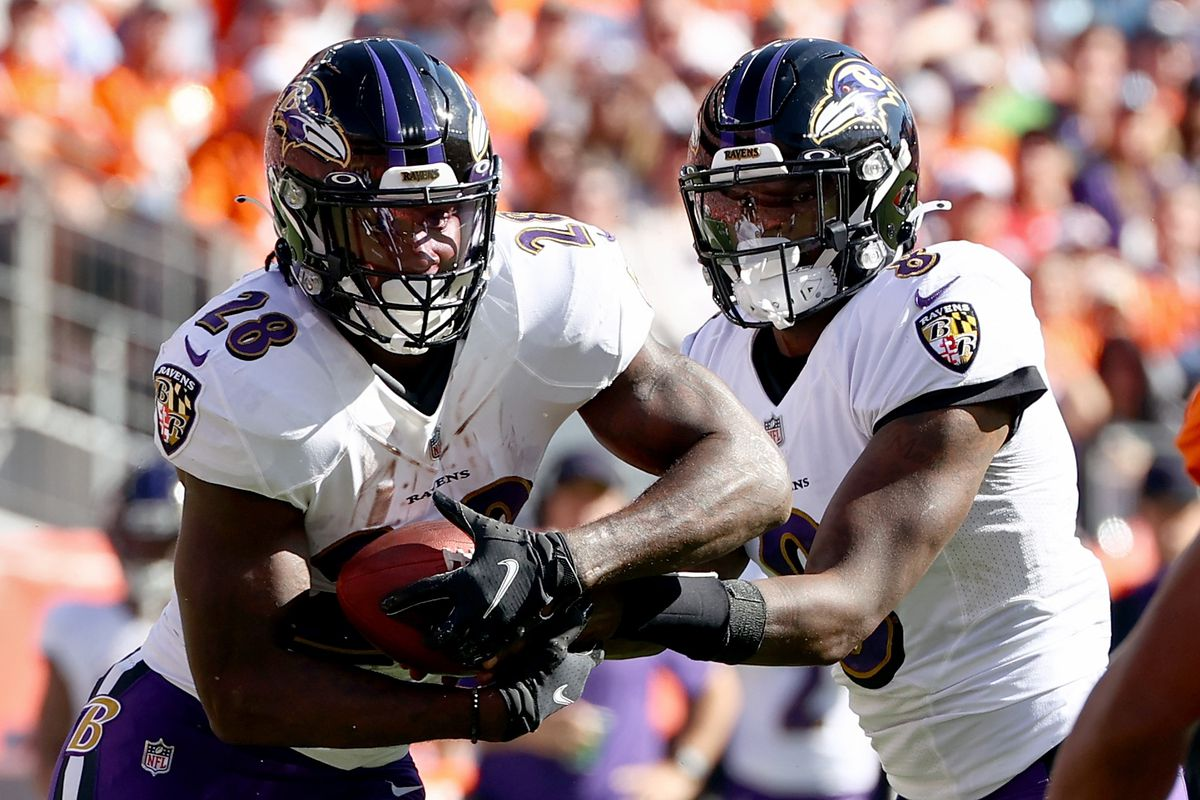 Quarterback Lamar Jackson #8 of the Baltimore Ravens hands the ball off to Latavius Murray #28 against the Denver Broncos in the first half at Empower Field At Mile High on October 03, 2021 in Denver, Colorado.