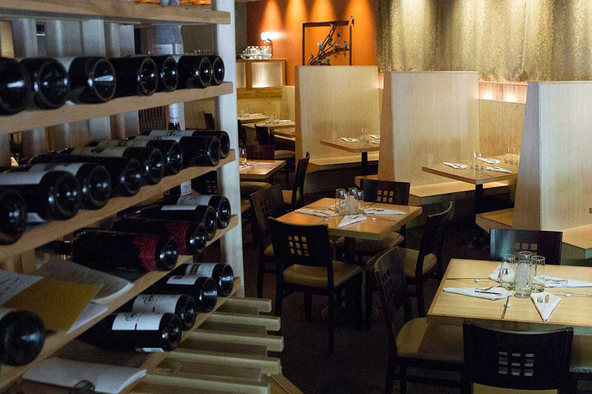 Wine bottles are displayed on a wooden rack in the empty dining room at Pacific Rim.