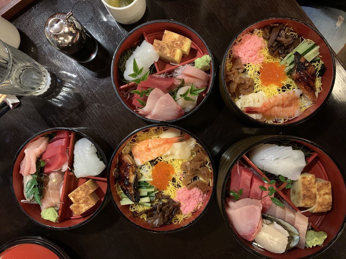 From above, a table filled with large bowls, some filled with sliced fish over rice, others segmented with sliced fish and other ingredients separate