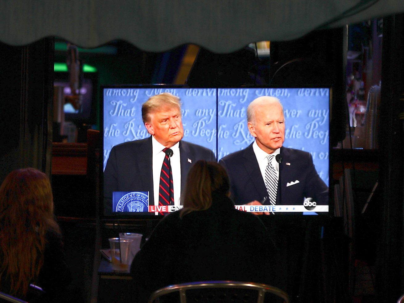 People watch the first 2020 presidential debate between Donald Trump and Joe Biden on a TV screen