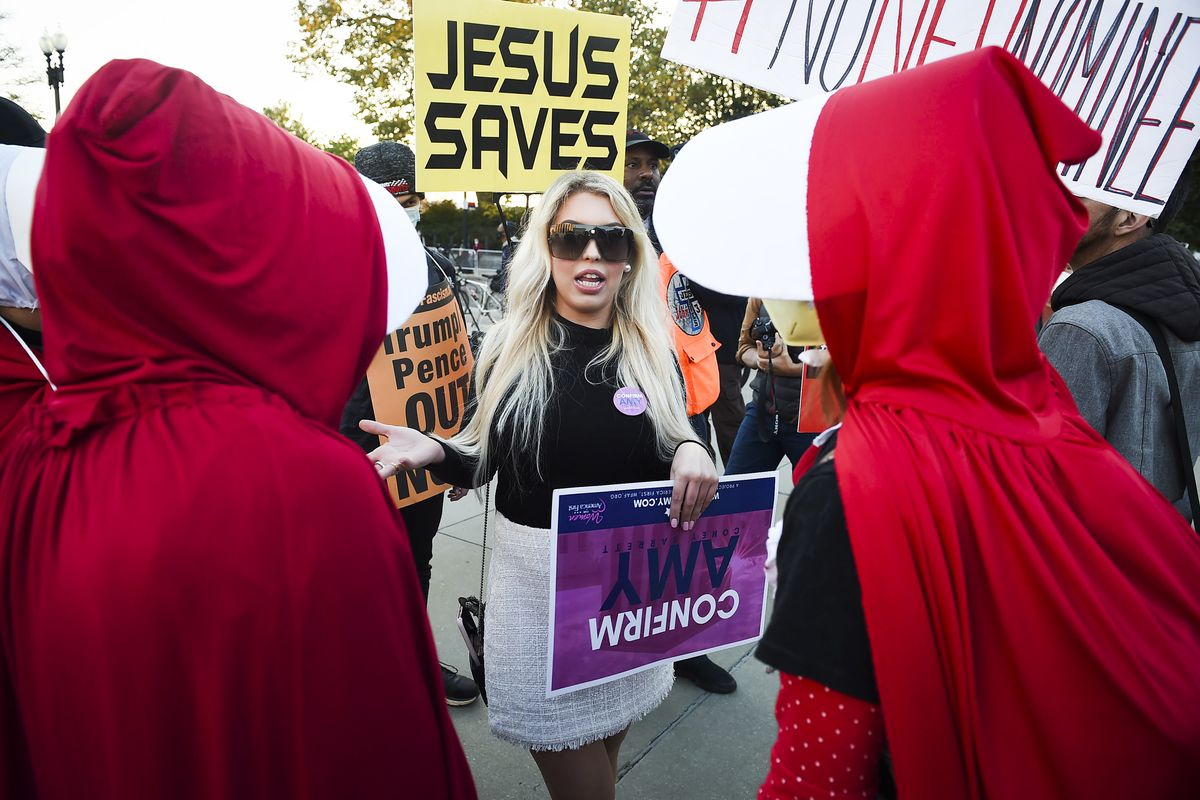 """Two people dressed in costumes reminiscent of """"The Handmaid's Tale"""" confront a person carrying a """"Confirm Amy"""" sign."""
