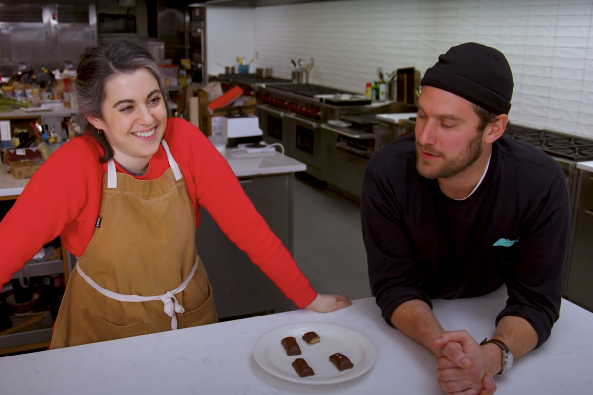 A white woman with black and white hair and a red shirt and apron next to a white man in a black shirt and black hat, in an industrial kitchen